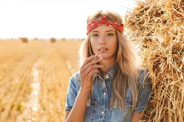 Immagine della splendida donna 20s in piedi vicino a un grande pagliaio in campo dorato e fumare sigarette durante la giornata di sole