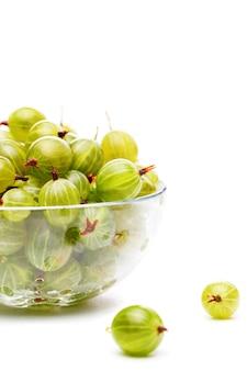 Immagine di uva spina verde in tazza di vetro su sfondo bianco vuoto in studio