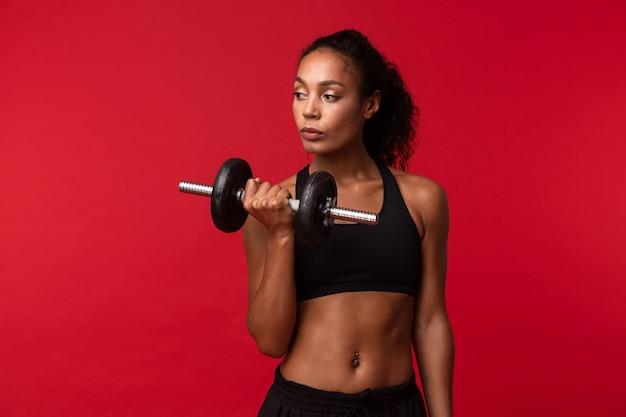 Immagine della donna afroamericana ginnastica in abiti sportivi neri sollevamento manubrio, isolato sopra la parete rossa