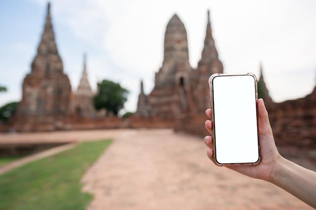 Immagine della mano che tiene il telefono cellulare con schermo bianco vuoto con pagoda.