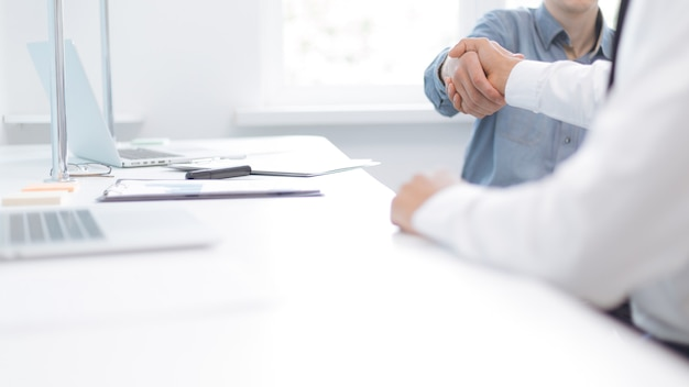 Immagine di una stretta di mano di uomini d'affari vicino al desktop. foto con una copia-spazio.