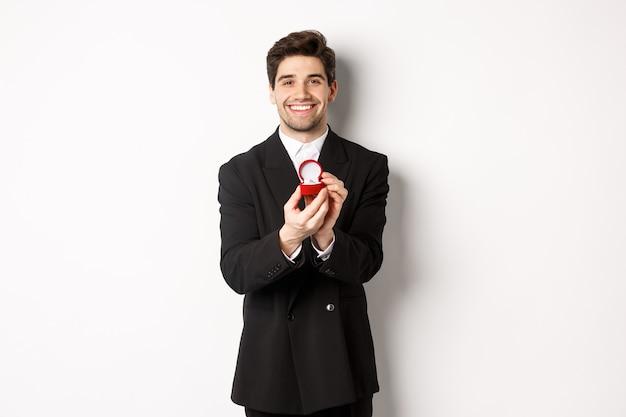 Immagine del bel ragazzo in abito nero che fa una proposta, chiede di sposarlo e mostra la fede nuziale, in piedi su sfondo bianco.