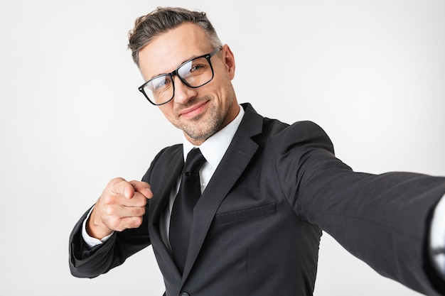 L'immagine di un bell'uomo d'affari isolato sopra il muro bianco prendere un selfie