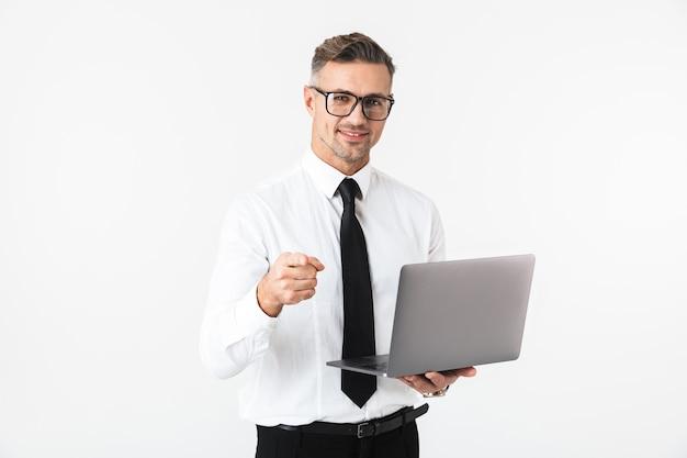 Immagine di un bell'uomo d'affari isolato su un muro bianco utilizzando computer portatile che punta.