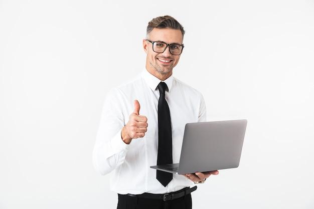 L'immagine di un bell'uomo d'affari isolato sopra il muro bianco utilizzando il computer portatile che mostra i pollici aumenta il gesto.