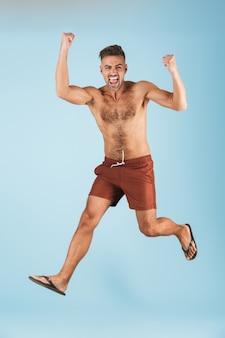 L'immagine di un uomo adulto felice emozionante bello in costume da bagno che posa sopra il salto blu della parete fa il gesto del vincitore.