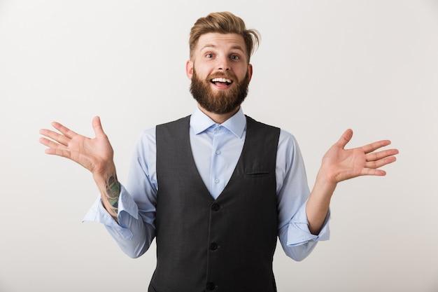 Immagine di un bel giovane uomo barbuto eccitato in piedi isolato sopra il muro bianco.