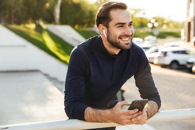 Immagine di un bel giovane sportivo forte e felice che posa all'aperto nella posizione del parco naturale utilizzando la musica d'ascolto del telefono cellulare con gli auricolari.