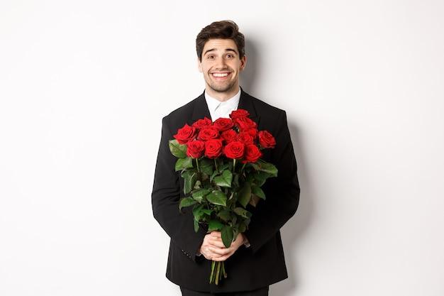 Immagine di un bell'uomo in abito nero, con in mano un mazzo di rose e sorridente, in piedi su sfondo bianco