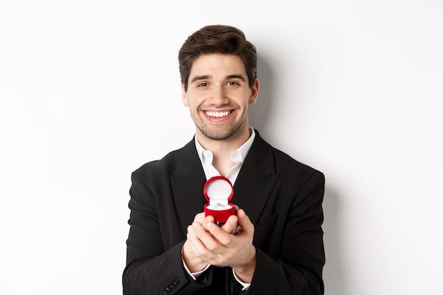 Immagine di un bell'uomo dall'aspetto romantico, piccola scatola aperta con anello di fidanzamento, che fa una proposta e sorride, in piedi su sfondo bianco.