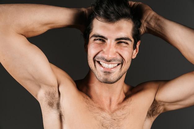 Immagine di un bel giovane uomo sorridente nudo in posa isolato.