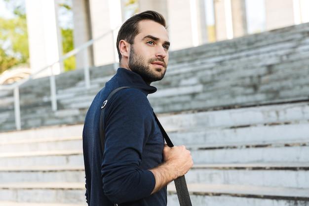 Immagine di un bel giovane sportivo forte e serio che posa all'aperto nella posizione del parco naturale che tiene in mano la borsa.