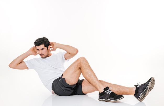 L'immagine dello sportivo bello in palestra fa esercizi sportivi sul pavimento sopra il muro bianco.