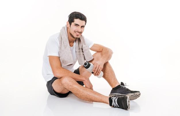 Immagine dello sportivo bello in palestra che si siede sul pavimento sopra la parete bianca. sorridere tenendo una bottiglia d'acqua.