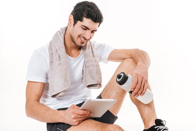 Immagine dello sportivo bello con l'asciugamano in palestra che si siede sul pavimento sopra la parete bianca. guarda il tablet e sorridi mentre tieni in mano una bottiglia d'acqua.