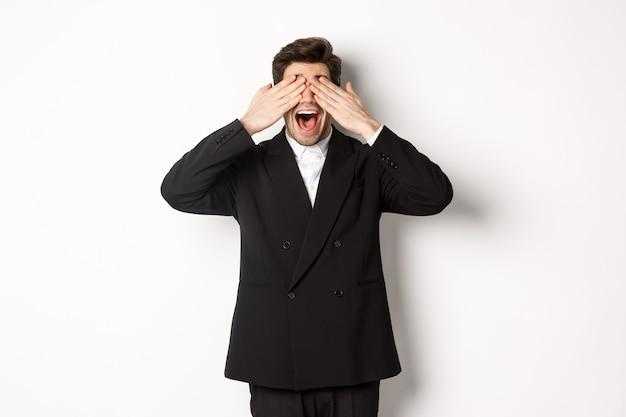Immagine di un bell'uomo elegante in abito nero, in attesa della sorpresa di natale, che copre gli occhi con le mani e sorride, anticipando i regali, in piedi su sfondo bianco