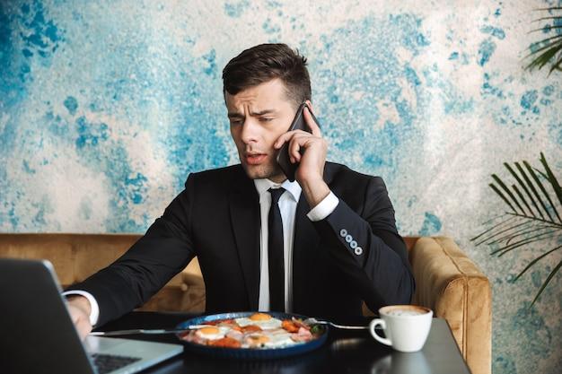 L'immagine di un bel giovane imprenditore seduto in un caffè utilizzando il computer portatile fare colazione o cenare mangiare parlando per telefono.