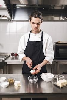 Immagine di un bel giovane cuoco chef presso la cucina che cucina al chiuso.