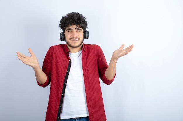 Immagine del bel giovane in cuffie ascoltando la canzone sul muro bianco.