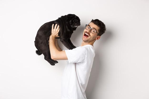 Immagine del bel giovane che ama il suo pug.