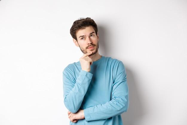 Immagine del bel giovane che fa la scelta, pensa e guarda pensieroso, in piedi su sfondo bianco.