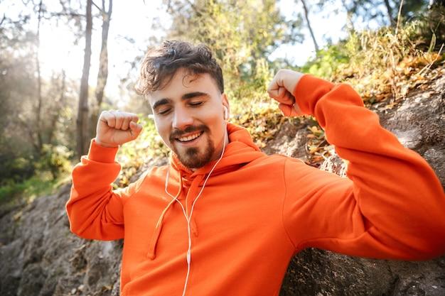 Immagine del corridore uomo di fitness sportivo giovane bello all'aperto nel parco ascoltando musica con gli auricolari.
