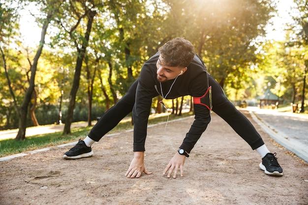 L'immagine del corridore dell'uomo di fitness sportivo giovane bello all'aperto nel parco fa esercizi.