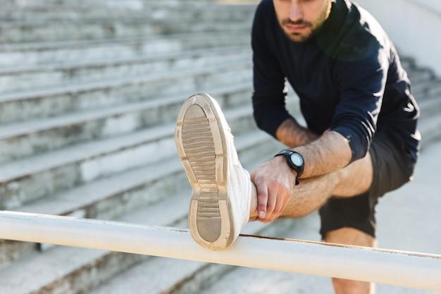 L'immagine di un bel giovane sportivo forte che posa all'aperto nel parco naturale fa esercizi di stretching.
