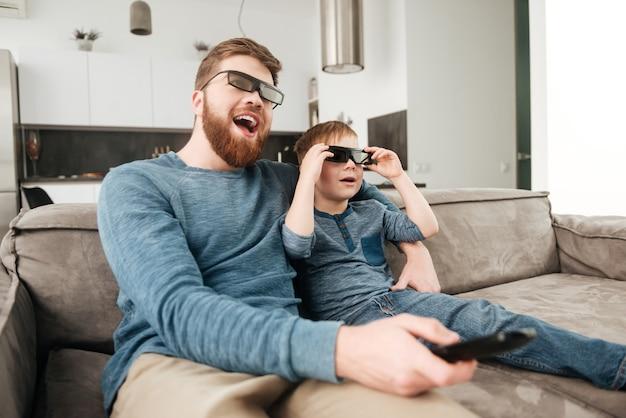 Immagine di un padre barbuto felice che tiene il telecomando mentre guarda la tv con il suo piccolo figlio carino che usa occhiali 3d.