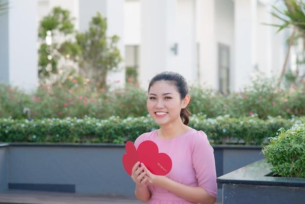 Immagine di una bella donna felice che legge una cartolina romantica con un grande cuore rosso, una donna attraente ha un biglietto di auguri sensuale, giorno di san valentino, concetto di amore