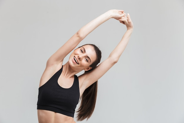 L'immagine di una bella giovane donna di forma fisica felice di sport fa gli esercizi isolati sopra la parete grigia.