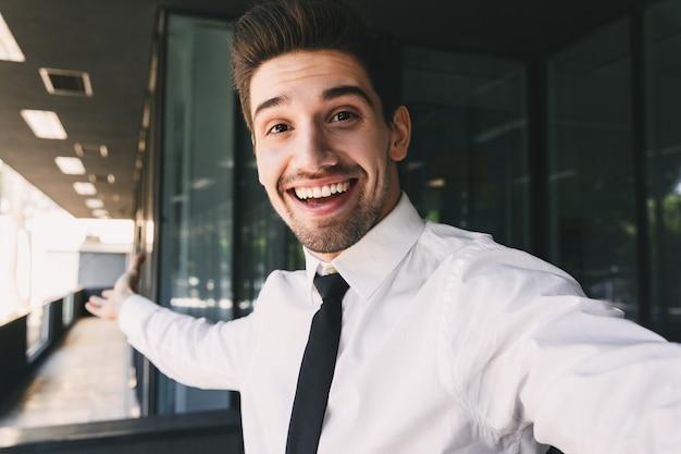 Immagine di uomo d'affari felice vestito in abito formale in piedi fuori dall'edificio di vetro e prendendo foto selfie