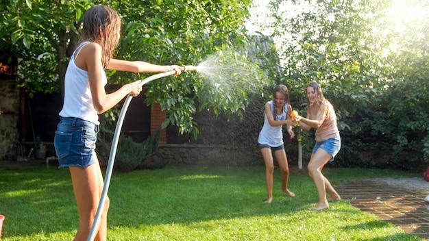 Immagine della famiglia allegra felice che gioca nel giardino del cortile. persone che spruzzano acqua con pistole ad acqua e tubo da giardino.