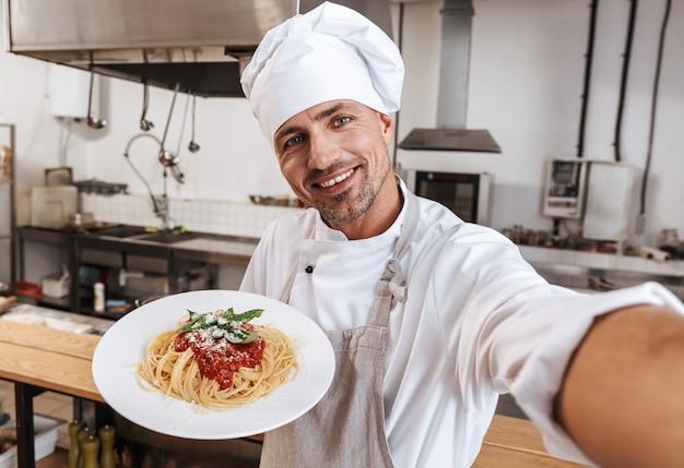 Immagine del capo uomo felice in grembiule tenendo selfie, mentre si trova in cucina nel ristorante