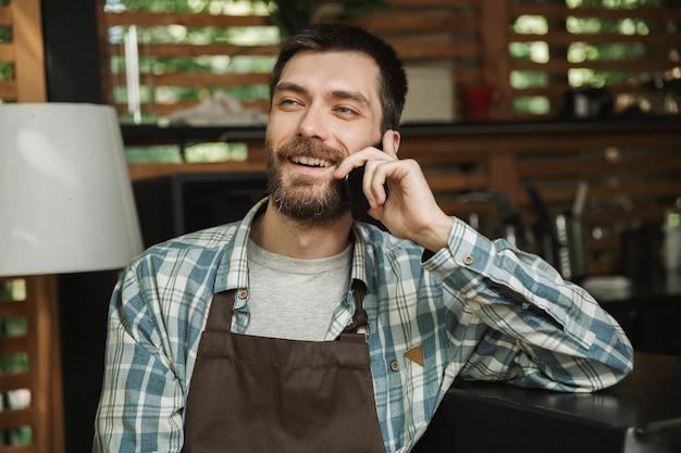 Immagine di un cameriere felice che indossa un grembiule seduto al bar e usa il cellulare mentre lavora al bar o al caffè all'aperto