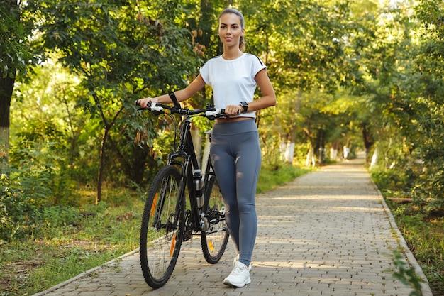Immagine della donna felice 20s che cammina con la bicicletta attraverso il parco verde, durante la giornata di sole