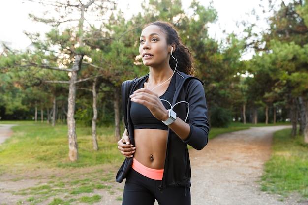 Immagine di una donna felice di 20 anni che indossa tuta nera e auricolari che si allenano, mentre attraversano il parco verde