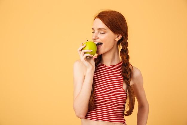 L'immagine di una giovane bella donna rossa felice che posa isolata sopra la parete gialla mangia la mela.