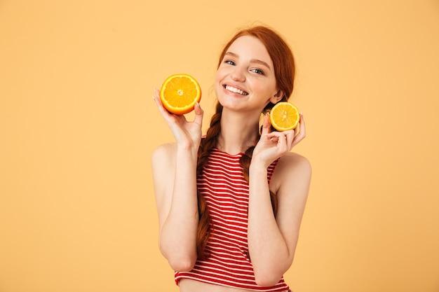 Immagine di una giovane bella donna rossa felice in posa isolata sul muro giallo che tiene l'arancia.