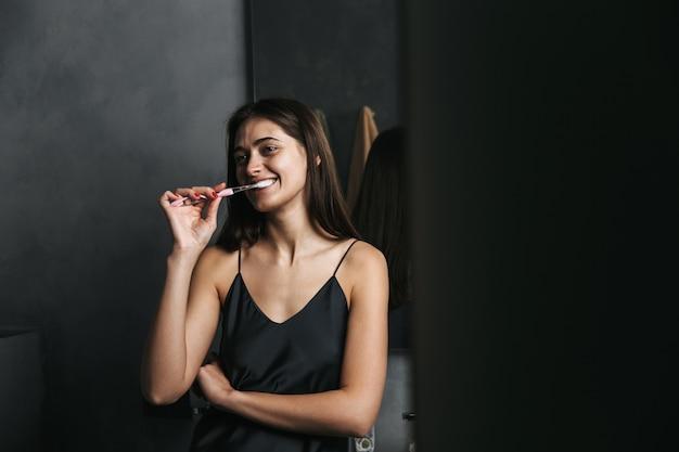 Immagine di una giovane bella donna felice in bagno lavarsi i denti.