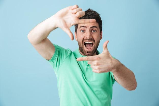 L'immagine di un giovane uomo barbuto bello felice che posa isolato sopra la parete blu fa il gesto della cornice fotografica.