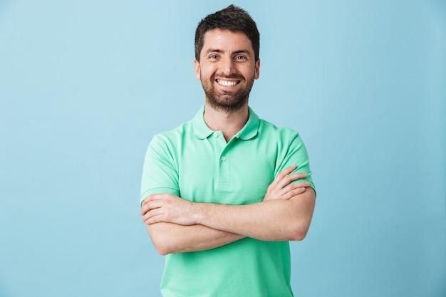 Immagine di un giovane uomo barbuto bello felice che posa isolato sopra la parete blu.