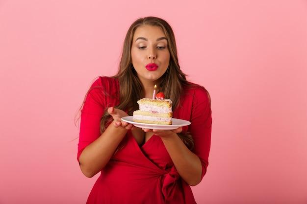 Immagine di una giovane donna felice isolata sopra la torta rosa della tenuta della parete.