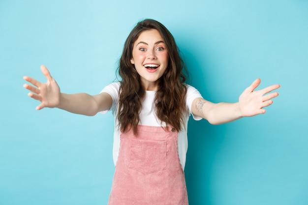 Immagine di una giovane donna felice con i capelli ricci e un bel trucco estivo, allungare le mani per abbracciare o tenere qualcuno, raggiungere gli abbracci, darti il benvenuto, sfondo blu.