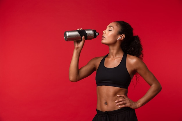 Immagine della donna afroamericana in buona salute in abiti sportivi neri che tengono la bottiglia d'acqua, isolata sopra la parete rossa