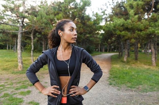 Immagine di una donna in buona salute 20s che indossa tuta nera e auricolari che si allenano, mentre attraversano il parco verde