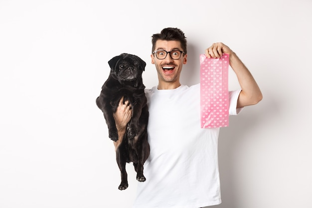 Immagine del proprietario dell'animale domestico ragazzo hipster, che tiene un carlino nero carino e un sacchetto di cacca di cane, in piedi su bianco.
