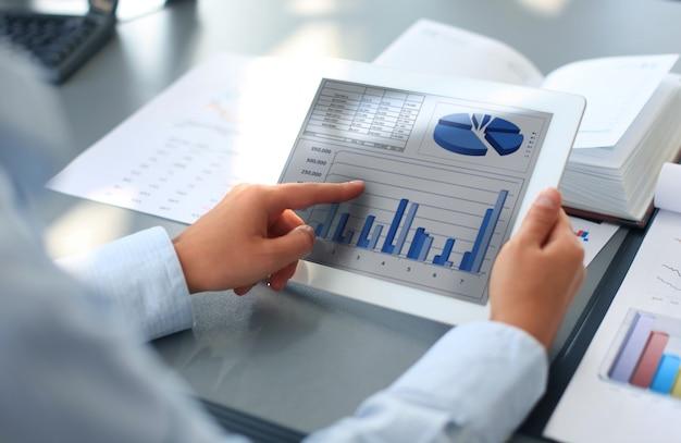 Immagine della mano umana che punta al touchscreen nell'ambiente di lavoro durante la riunione