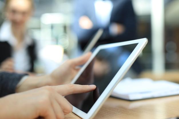 Immagine della mano umana che punta al touchscreen nell'ambiente di lavoro durante la riunione.