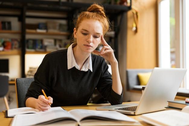 Immagine della ragazza intelligente che studia, mentre è seduto alla scrivania nella biblioteca del college con la parete dello scaffale